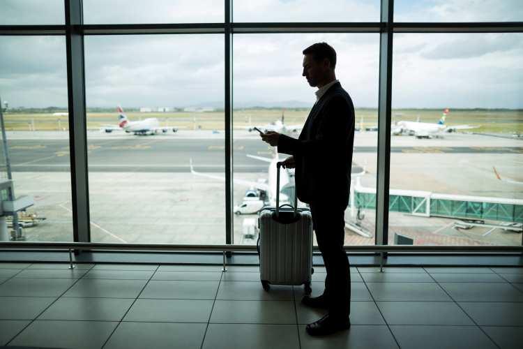 空港でスーツケースを持って搭乗口に向かっている