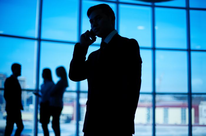 会社の上司に電話で後悔していることを伝えているスーツの男性