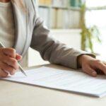 弁護士がデスクで書類にサインをしている