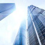 下から見上げた都心の高層ビルと眩しい太陽の光