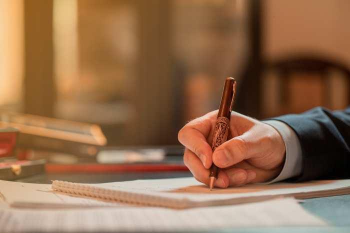 便箋に万年筆で退職届を書く銀行員