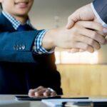 オフィスで握手をする2人のビジネスマン