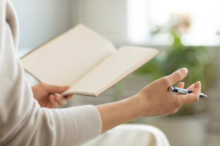 ノートに書いている退職代行の流れを解説している女性